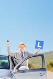 Homme mûr heureux à côté de la voiture tenant un L signe et clé après havi Photographie stock