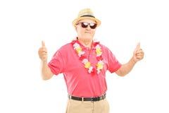 Homme mûr heureux avec le chapeau et les lunettes de soleil renonçant à des pouces Photo libre de droits