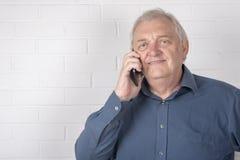 Homme mûr heureux parlant au téléphone avec un fond blanc de brique Image stock