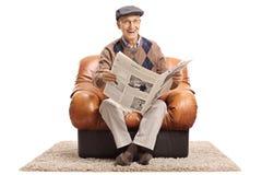 Homme mûr joyeux avec le journal se reposant dans le fauteuil en cuir images stock