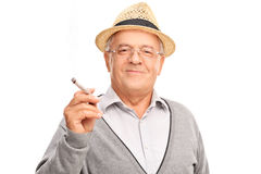 Homme mûr joyeux tenant un joint Photographie stock