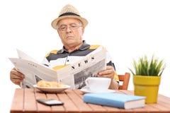 Homme mûr lisant un journal posé à une table basse Images libres de droits