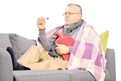 Homme mûr malade sur un sofa avec une bouteille d'eau chaude regardant Image stock