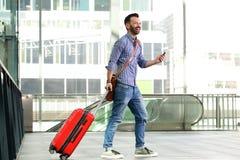 Homme mûr marchant à la station avec le sac et le téléphone portable Images libres de droits