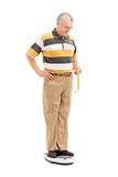Homme mûr mesurant sa taille Image libre de droits