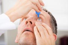 Homme mûr mettant des gouttes pour les yeux dans les yeux Photo stock