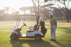 Homme mûr mettant le club de golf dans le sac Photographie stock