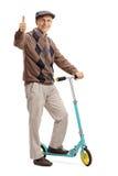 Homme mûr posant avec le scooter et composant le pouce Images libres de droits