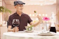 Homme mûr regardant une salade dans le dégoût Images stock