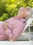 Homme mûr reposant sur la chaise longue Photos stock