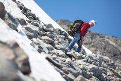 Homme mûr s'élevant en montagne à la saison d'été, se reposant sur la pente raide Photos libres de droits