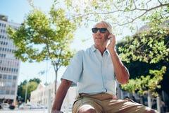 Homme mûr s'asseyant dehors dans la ville faisant un appel téléphonique Images libres de droits