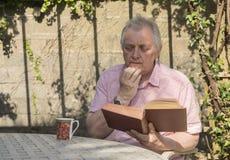 Homme mûr s'asseyant en dehors de lire un livre Photographie stock