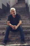 Homme mûr s'asseyant sur des étapes à l'arrière-plan urbain Photo stock