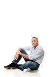 Homme mûr s'asseyant sur le plancher Images stock