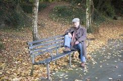 Homme mûr s'asseyant sur un banc de parc Photo stock