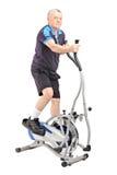 Homme mûr s'exerçant sur une machine croisée d'entraîneur Photo stock