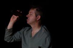 Homme mûr sale déprimé buvant d'une bière à l'arrière-plan foncé Image stock