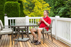 Homme mûr se reposant dans la chaise sur le patio extérieur avec la tasse de café Photographie stock