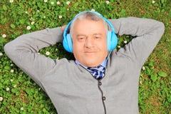 Homme mûr se trouvant sur l'herbe avec des écouteurs, écoutant la musique photographie stock
