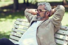 Homme mûr songeur s'asseyant sur le banc en parc urbain Photos stock