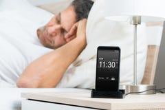 Homme mûr sur le lit avec l'alarme sur l'écran de téléphone portable image libre de droits