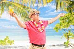 Homme mûr tenant un cocktail et faisant des gestes la joie Images libres de droits
