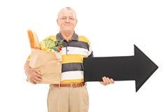 Homme mûr tenant un sac d'épicerie et une flèche Photographie stock libre de droits