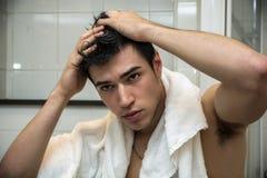 Homme magnifique après sa douche tenant sa tête photo libre de droits