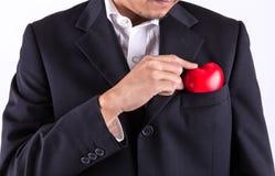 Homme maintenant le coeur rouge dans la poche de costume Photographie stock