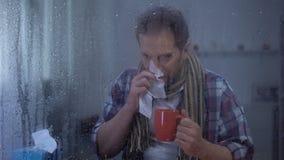Homme malade éternuant et buvant du thé chaud à la maison derrière la fenêtre pluvieuse, virus de grippe banque de vidéos