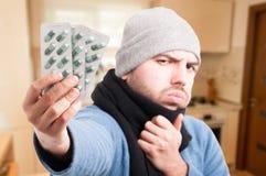 Homme malade avec des bandes de comprimé sur sa main Photos stock