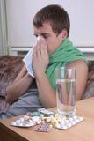 Homme malade avec la glace d'american national standard de tablettes de l'eau Images stock