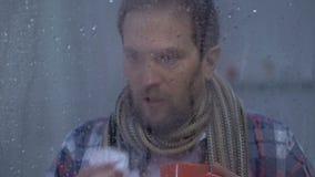 Homme malade buvant la boisson chaude, éternuant et regardant à la caméra, traitement de grippe banque de vidéos