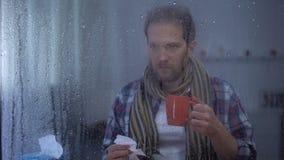 Homme malade dans l'écharpe éternuant et buvant du thé chaud à la maison le jour pluvieux, virus de grippe banque de vidéos