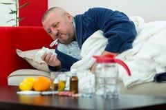 Homme malade dans le lit avec les drogues et le fruit sur la table Photo stock