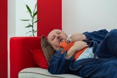Homme malade dans le lit ayant un mal de tête tenant une bouteille d'eau chaude Image stock