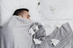 Homme malade dans le lit entouré par les tissus utilisés photographie stock libre de droits