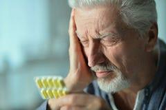 Homme malade plus âgé avec des pilules à disposition Photographie stock libre de droits