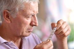 Homme malade plus âgé avec des pilules Images stock