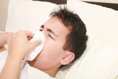 Homme malade soufflant son nez Image stock