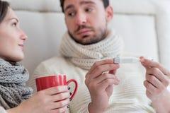 Homme malade triste tenant un thermomètre Photo stock