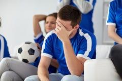 Homme malheureux avec des amis ou des passionés du football à la maison Photo stock
