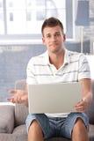 Homme malheureux avec l'ordinateur portatif à la maison Photo stock
