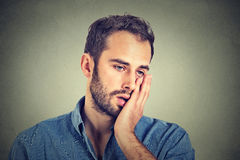 Homme malheureux désespéré sur le fond gris de mur Image libre de droits