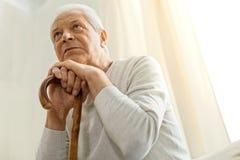 Homme malheureux réfléchi se penchant sur un bâton de marche Image libre de droits