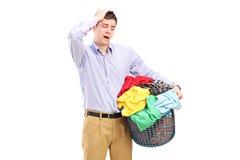 Homme malheureux regardant un panier complètement de blanchisserie Images stock