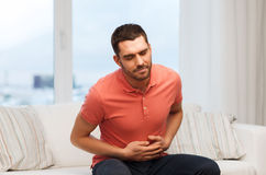Homme malheureux souffrant du mal d'estomac à la maison Photos stock
