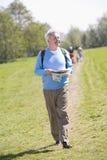 Homme marchant à l'extérieur retenant le sourire de carte Photo stock