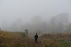 Homme marchant à une ville en brouillard images libres de droits